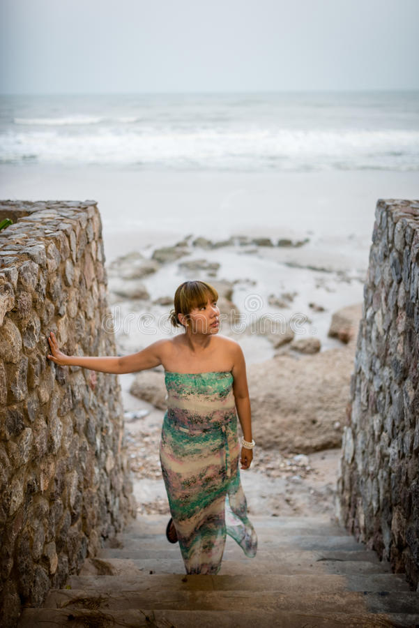 Título: Mulheres na praia, nas escadas de pedra e na passagem conduzindo para baixo em uma praia Hua Hin, Tailândia fotografia de stock royalty free