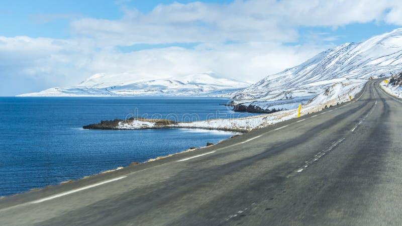 Título vazio da estrada nas montanhas nevado com um lago em um lado imagens de stock royalty free