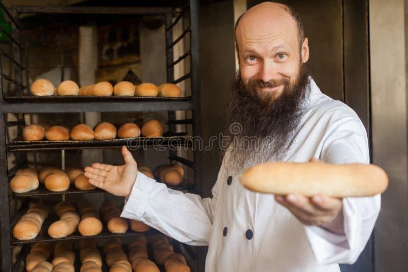 Tómelo por favor Retrato del panadero adulto joven positivo atractivo con la barba larga en la situación uniforme blanca en su lu imagen de archivo libre de regalías