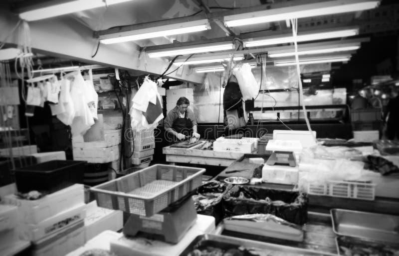 TÓQUIO 26 DE NOVEMBRO: Trabalhador que processa peixes no mercado do marisco da venda por atacado de Tsukiji fotos de stock royalty free