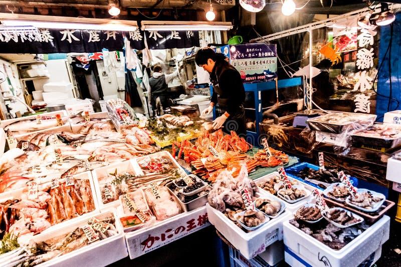 Tóquio, Japão - 15 de janeiro de 2010: Amanhecer no mercado de peixes de Tsukiji Trabalhador que apresenta peixes frescos e maris fotografia de stock royalty free