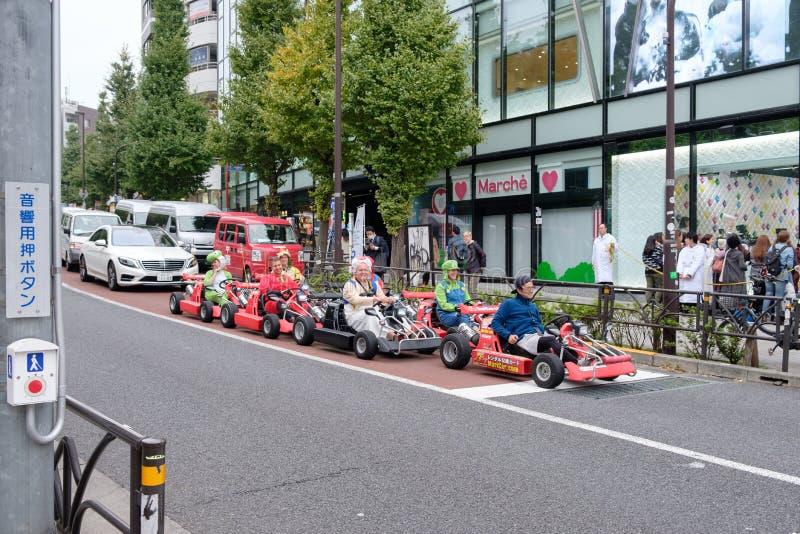 Tóquio, Japão - 8 de novembro de 2017: O estrangeiro dos turistas com condução do traje dos desenhos animados vai-kart em tokyo imagens de stock royalty free