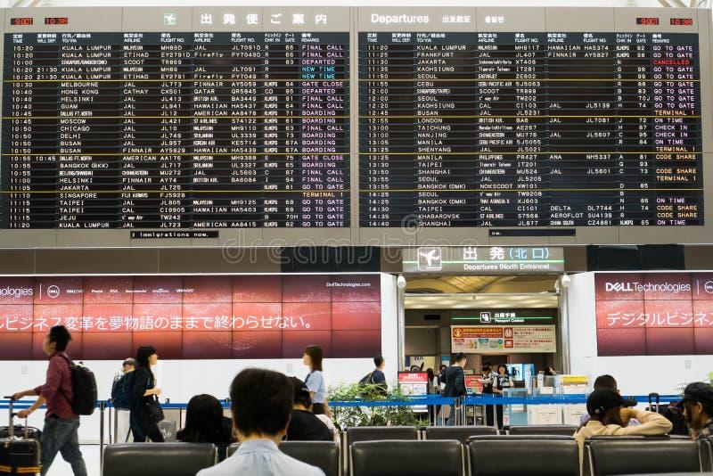 Tóquio, Japão - 9 de outubro de 2018: Esperando alguém ao olhar a programação de voo fotografia de stock