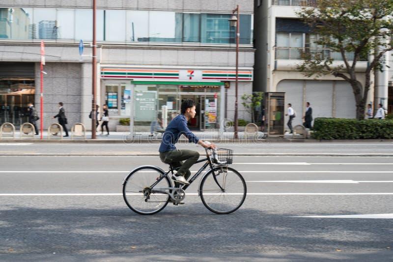 Tóquio, Japão - 9 de outubro de 2018: um cidadão que monta uma bicicleta alugada que apressa-se para ir trabalhar imagem de stock royalty free