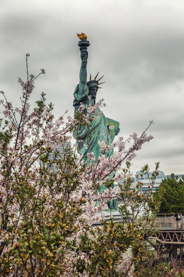 Tóquio, Japão, 04/08/2017: Estátua da liberdade na ilha de Odaiba em Sakura Flowers, fotografia de stock royalty free