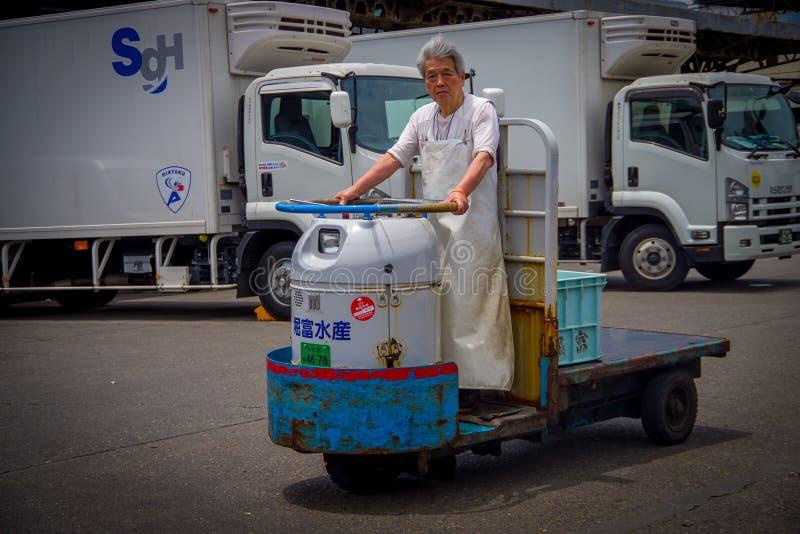 TÓQUIO, JAPÃO O 28 DE JUNHO - 2017: O ancião não identificado que conduz uma máquina da carga fora no mercado de Tsukiji dos peix imagem de stock