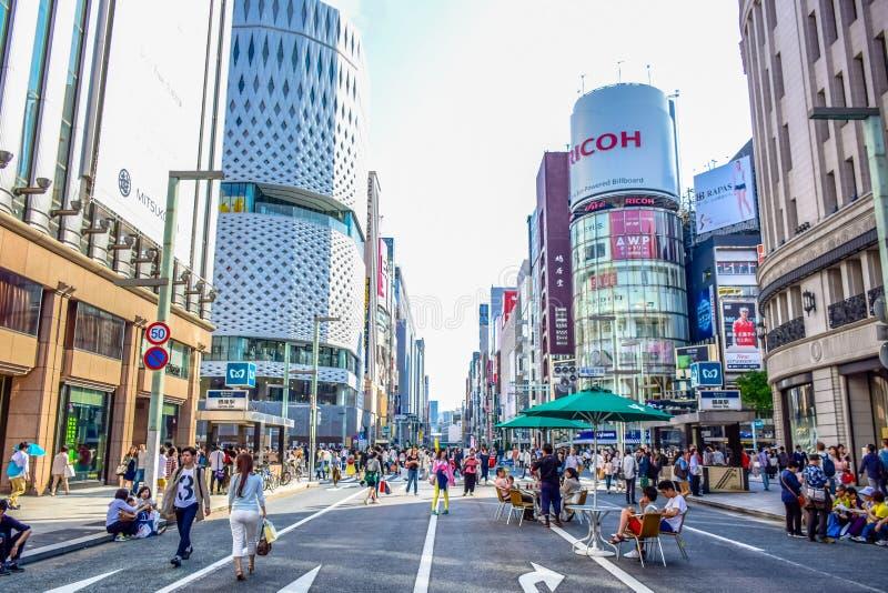 TÓQUIO, JAPÃO: Povos que passam seu tempo que visita a rua de Ginza, uma área de compra muito popular do Tóquio, durante o weeke imagens de stock royalty free