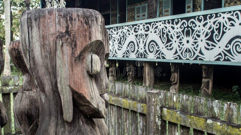 Tótem de madera tradicional de la escultura de Dayaknese delante de la casa tradicional de la tribu del Dayak en Pulau Kumala, In imagen de archivo libre de regalías