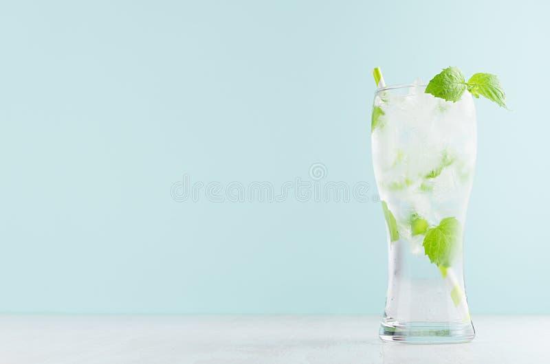 Tônico fresco saudável com hortelã verde, cubos de gelo, soda, palha listrada no vidro misted na tabela de madeira branca, cor ve fotos de stock