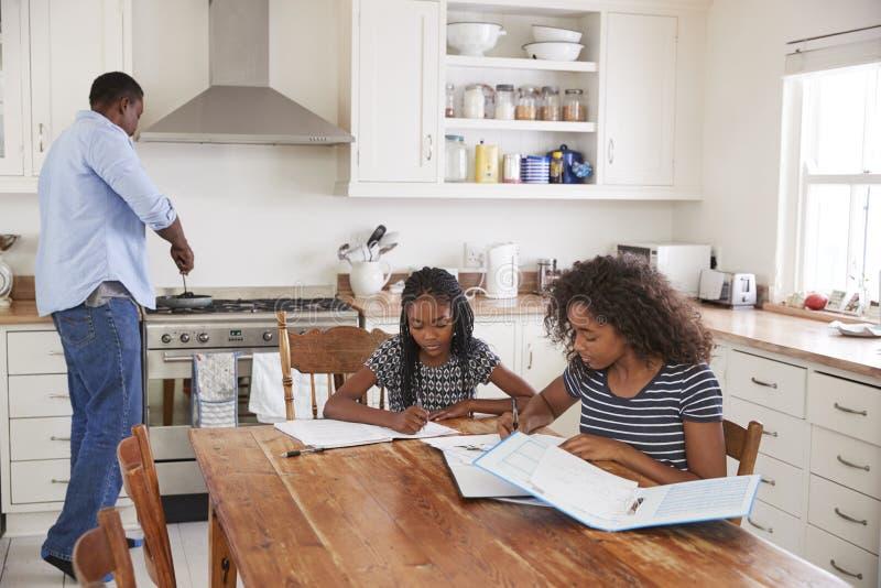 Töchter, die bei Tisch sitzen, Hausarbeit als Vater Cooks Meal tuend lizenzfreie stockfotos