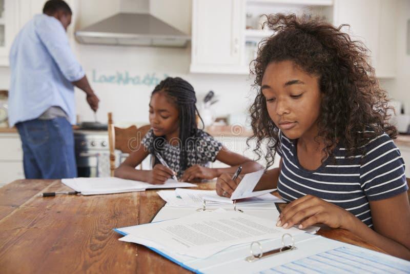 Töchter, die bei Tisch sitzen, Hausarbeit als Vater Cooks Meal tuend stockfoto