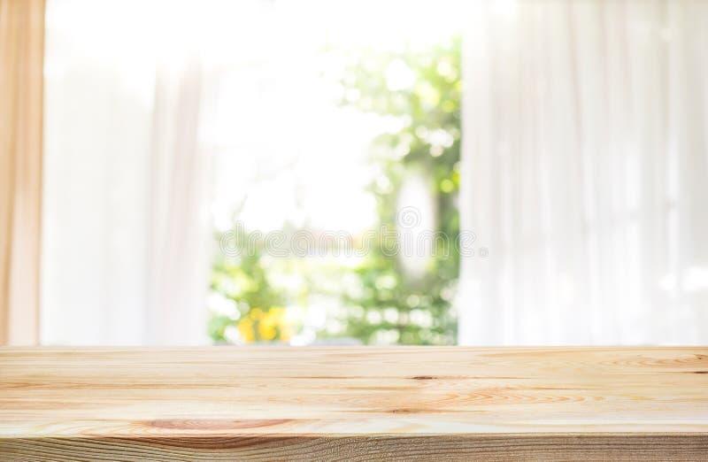Töm av den wood tabellöverkanten på suddighet av gardinfönstret och arbeta i trädgården royaltyfri fotografi