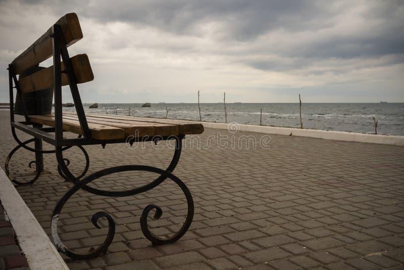 Töm bänken på promenaden i molnigt väder fotografering för bildbyråer