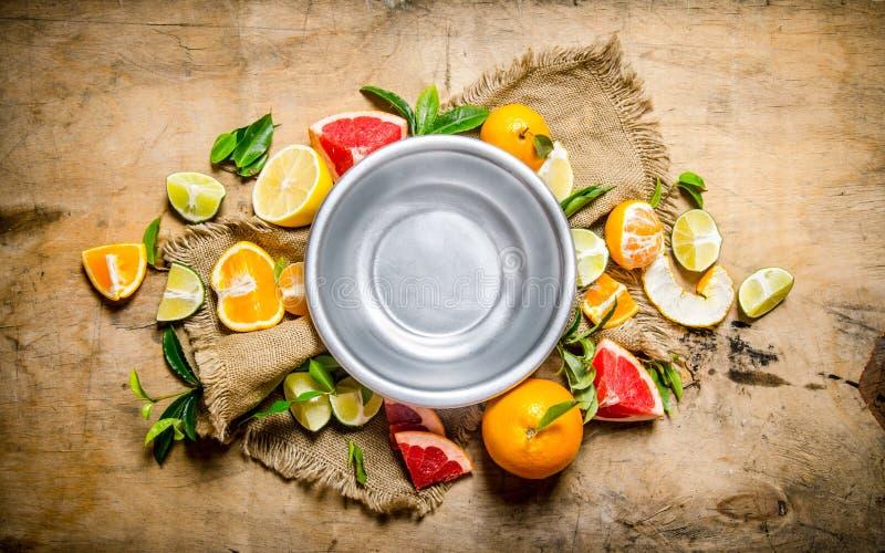 Töm bunken av frukt runt om citrus - grapefrukten, apelsinen, tangerin, citron, kalkar det gamla tyget arkivfoton