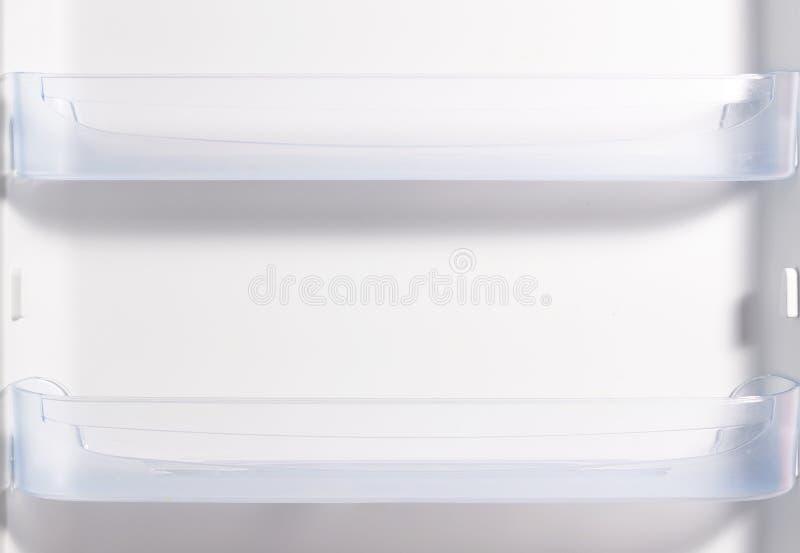 Töm den öppna kylen med hyllor, vit kylskåpbakgrund royaltyfria bilder