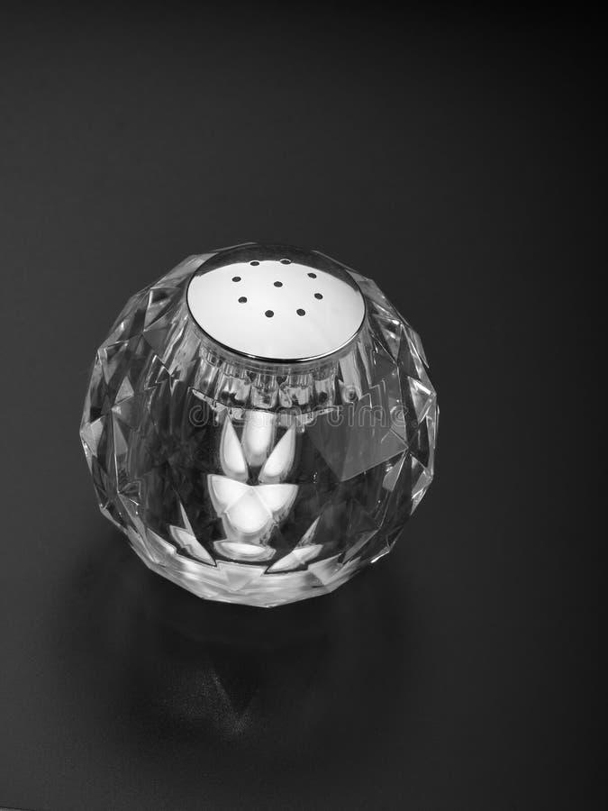 Töm den runda crystal salta shaker på en mörk bakgrund arkivfoton