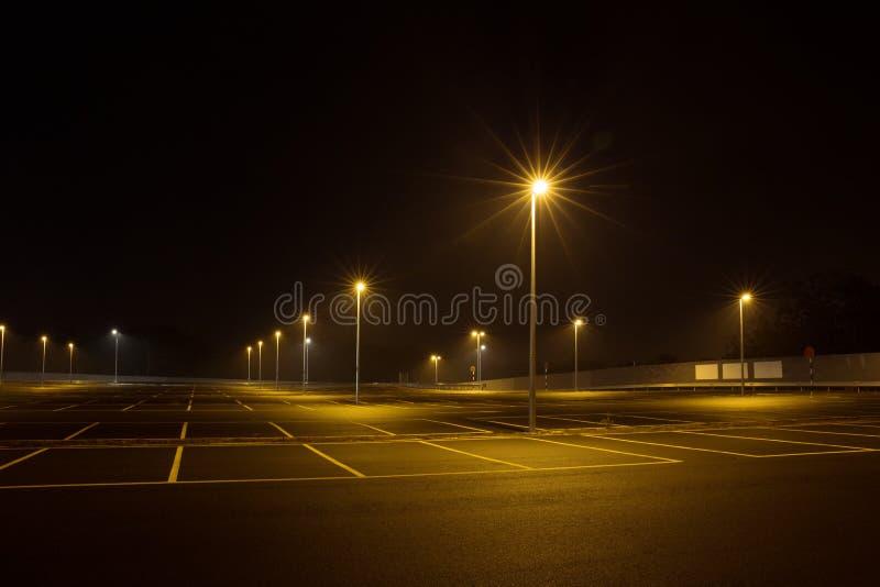Töm den utomhus- parkeringshuset på natten som skins med gatalampor royaltyfri bild