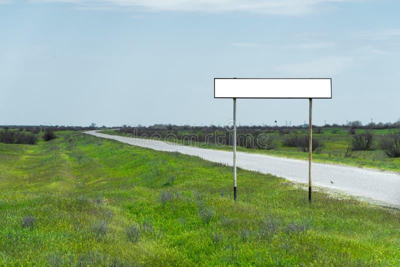 Töm det gamla vägmärket för namnet av en stad eller byn befolkat område nära vägen i bygden mot en blå himmel royaltyfri foto