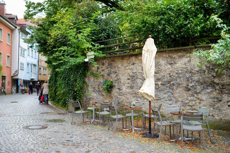Töm det utomhus- kafét på härlig regnig höstdag i Lindau, Tyskland Tomma chiars och tabeller under fallande regn i höst royaltyfri fotografi