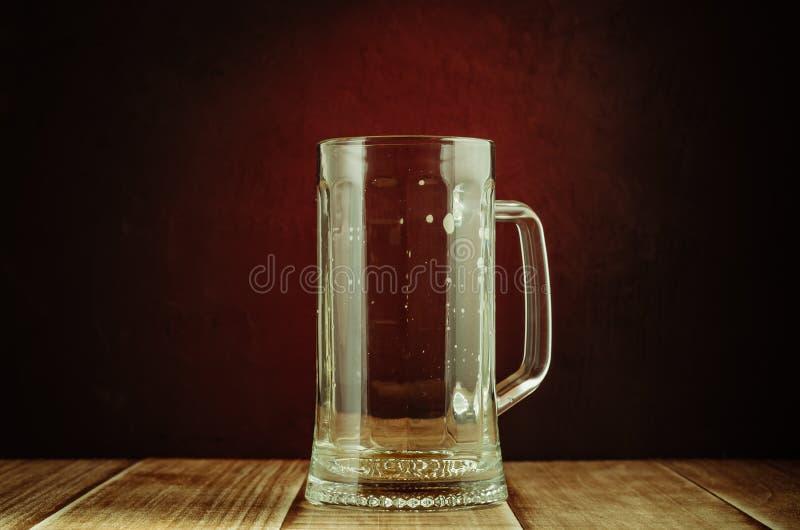 töm ett exponeringsglas från öl på en rött ljusbakgrund/töm ett exponeringsglas från öl på en trätabell och en röd bakgrund, sele royaltyfri bild