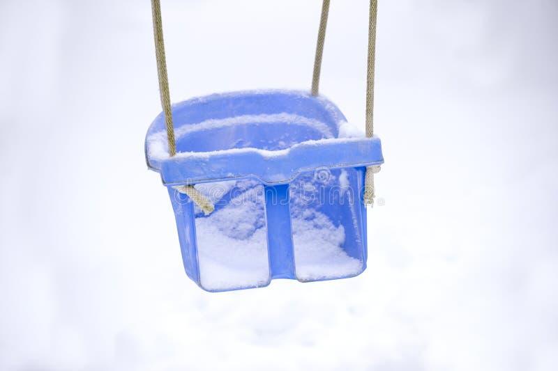 Töm gunga i vintertid med snö royaltyfria bilder