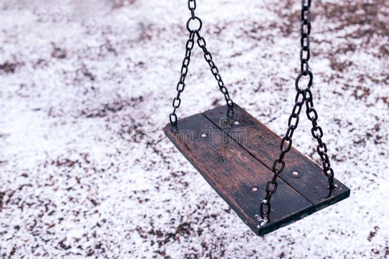 Töm gunga på barnlekplats under snö arkivbilder