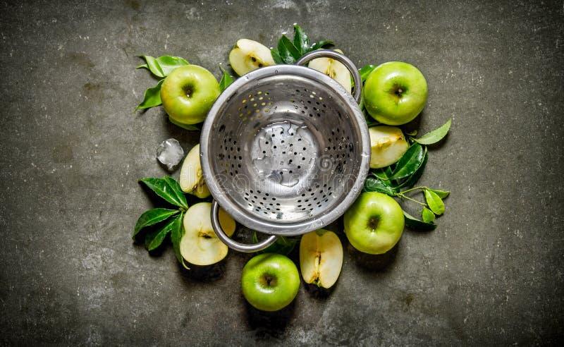 Töm koppen och göra grön äpplen med sidor arkivbilder