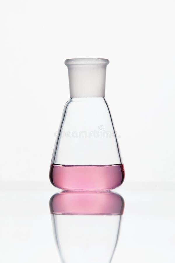 Töm mätningscylindern/buretten med graderade markeringar Exponeringsglas med rosa flytande på vit bakgrund royaltyfri foto