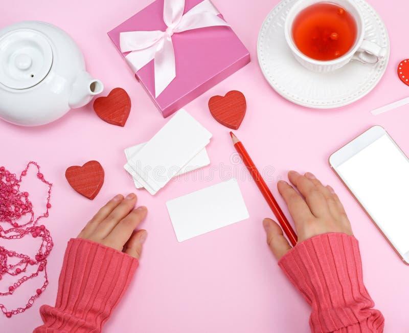 Töm pappers- affärskort och en röd blyertspenna, bredvid ` s för två kvinnor fotografering för bildbyråer