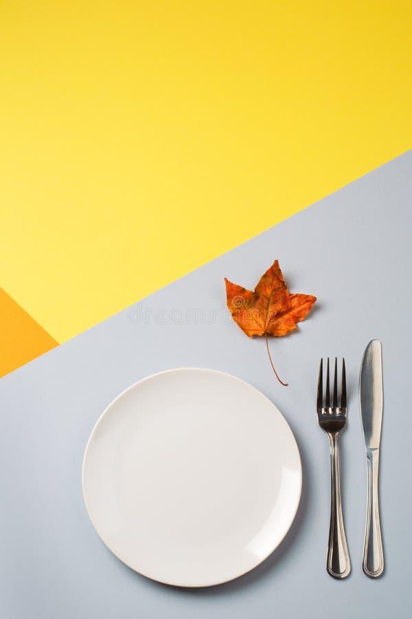Töm plattan och bestick på guling-apelsin-grå färger bakgrund begrepp av höstmenyn av ett kafé eller en restaurang royaltyfria bilder