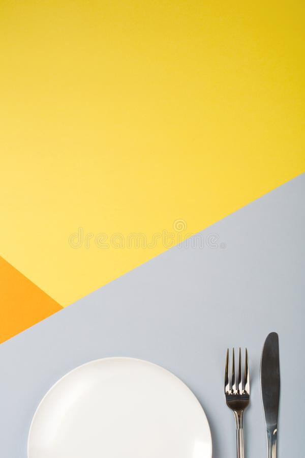 Töm plattan och bestick på guling-apelsin-grå färger bakgrund begrepp av höstmenyn av ett kafé eller en restaurang arkivfoto