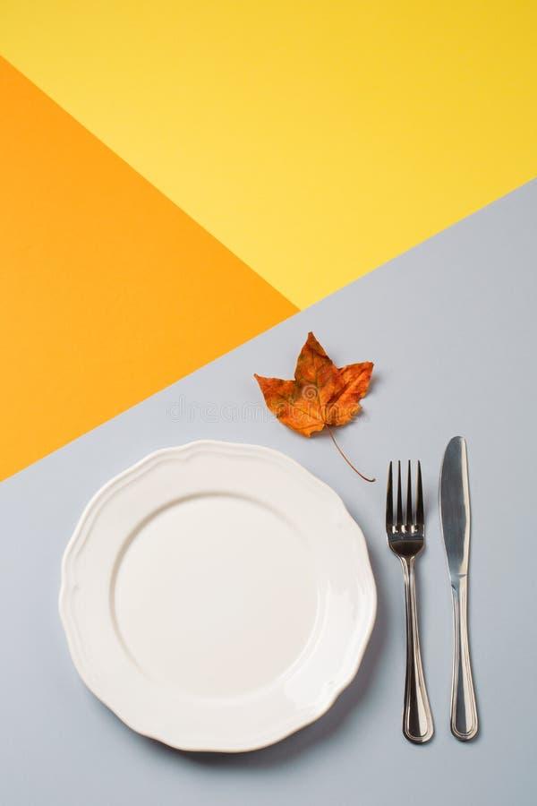 Töm plattan och bestick på guling-apelsin-grå färger bakgrund begrepp av höstmenyn av ett kafé eller en restaurang arkivbilder