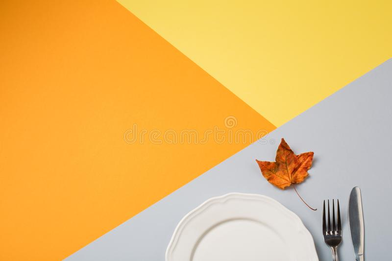Töm plattan och bestick på guling-apelsin-grå färger bakgrund begrepp av höstmenyn av ett kafé eller en restaurang arkivbild
