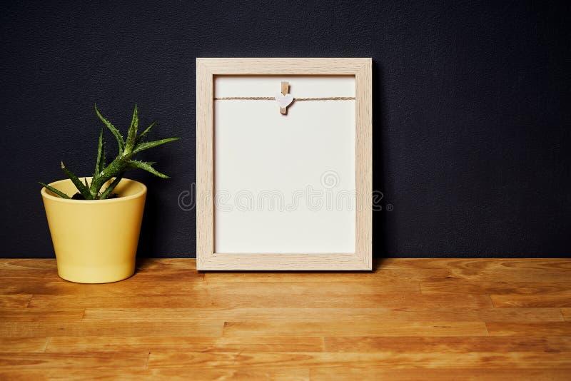 Töm ramen på en trähylla på en svart vägg arkivbild