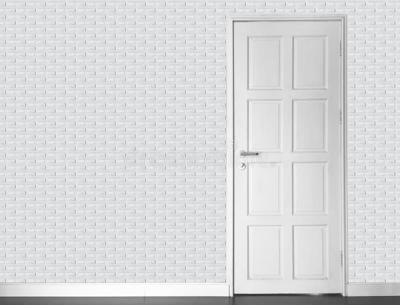 Töm rum - den vita tegelstenväggen för vinatge och den wood dörren och ol för vit arkivfoto