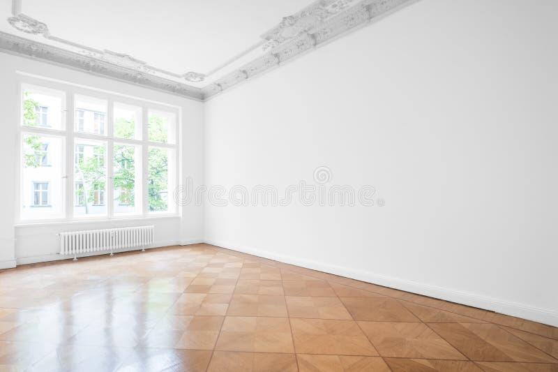 Töm rum med parkettgolvet, vita väggar och stuckaturtaket royaltyfria foton