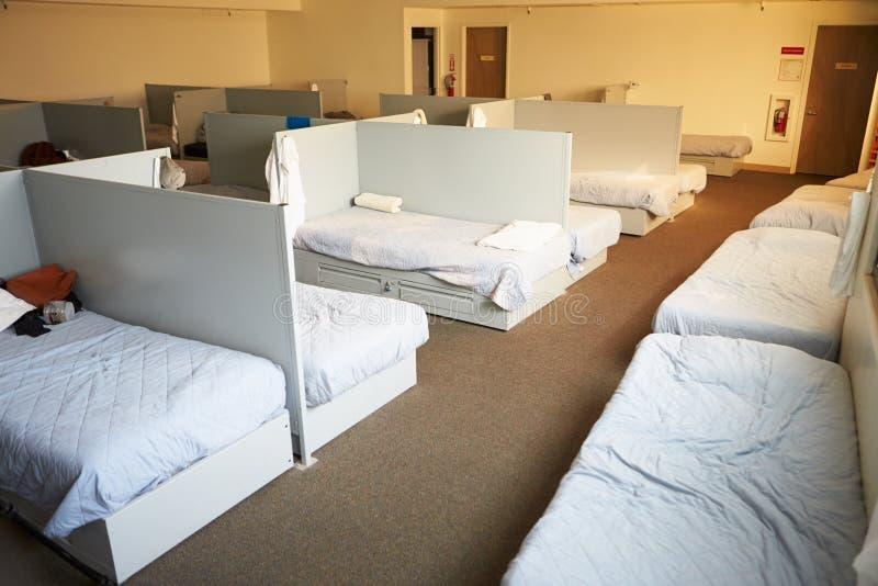 Töm sängar i hemlöst skydd royaltyfri foto