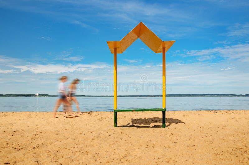 Töm stranden med en bänk med en markis på kusten arkivbilder