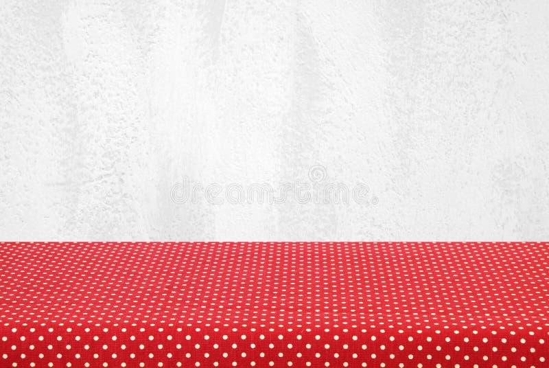 Töm tabellen som täckas med den röda prickbordduken över vit cem royaltyfria bilder