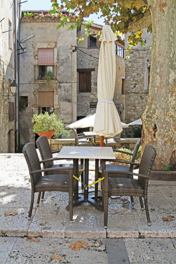 Töm terrassen med platser och parasoller från en restaurang i skuggan på bakgrunden av den gamla staden Besalu royaltyfri foto
