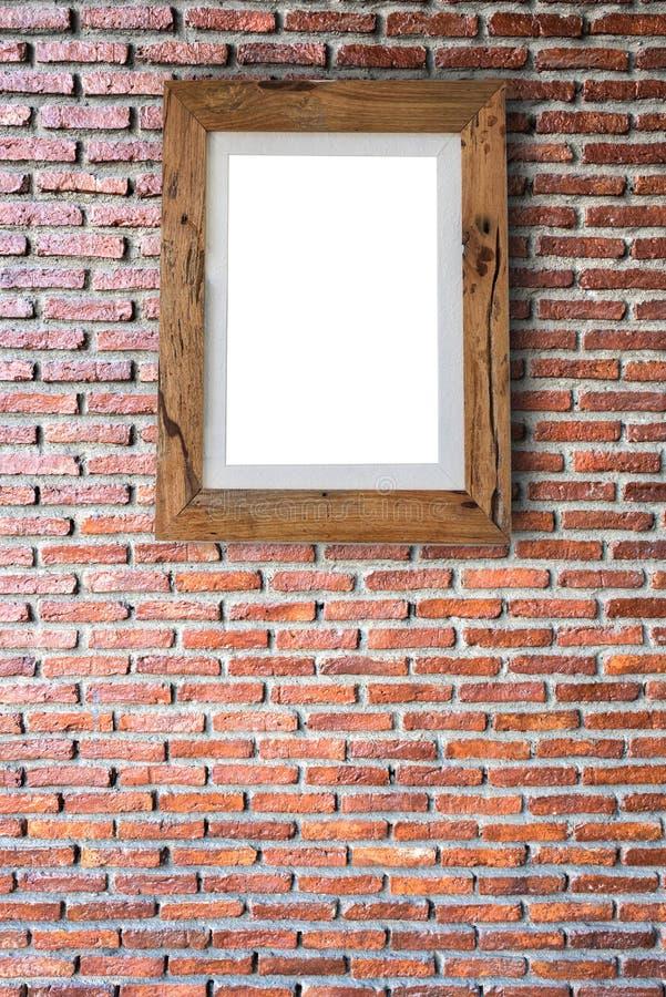 Töm träbildramen som hänger på en tegelstenvägg arkivbild