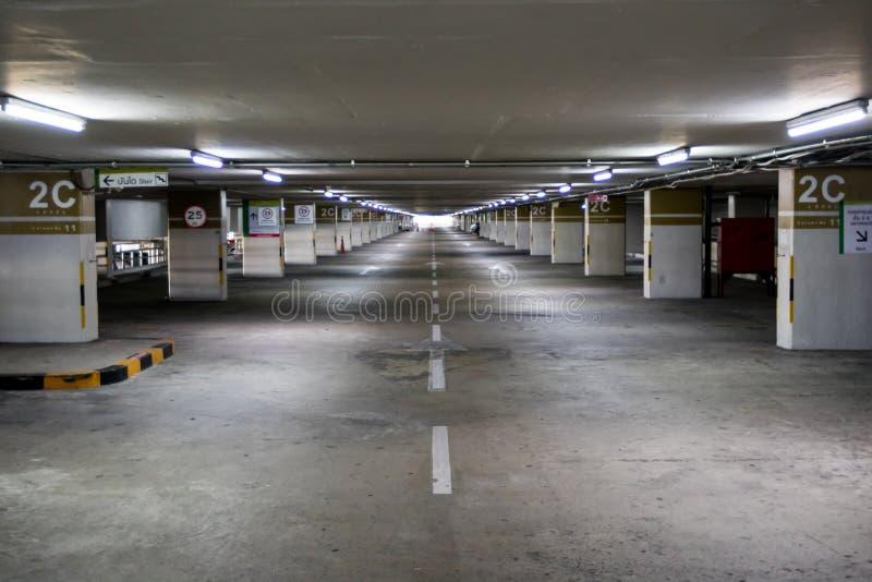 Töm utrymmeparkeringshusinre på eftermiddagen Inomhus parkeringsplats inre av parkeringsgaraget med bilen och den vakanta parkeri fotografering för bildbyråer