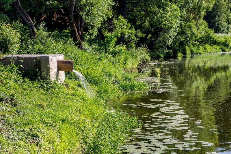 Töm vatten från röret in i floden arkivfoton