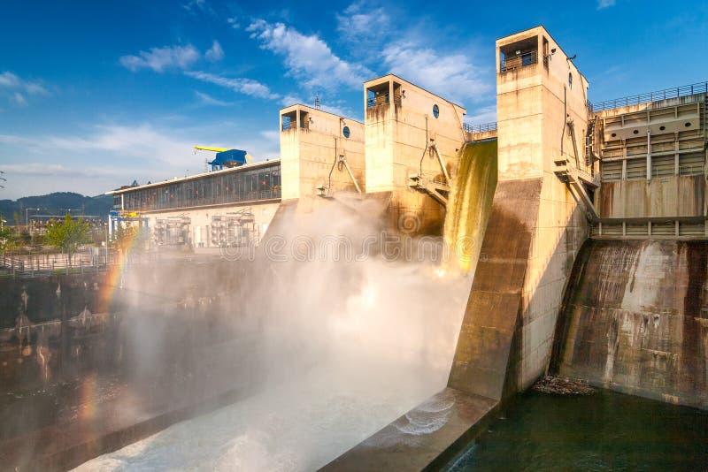 Tömning av vatten med regnbågen från den hydroelektriska fördämningen arkivfoton