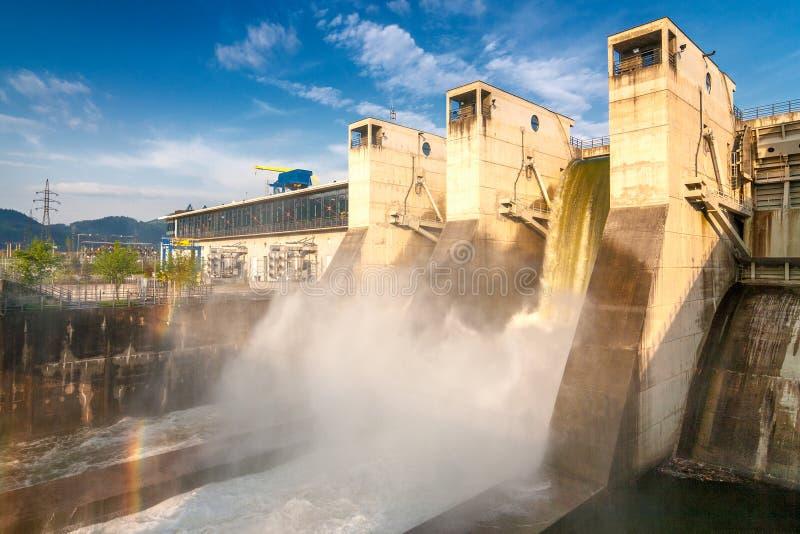 Tömning av vatten med regnbågen från den hydroelektriska fördämningen royaltyfria foton