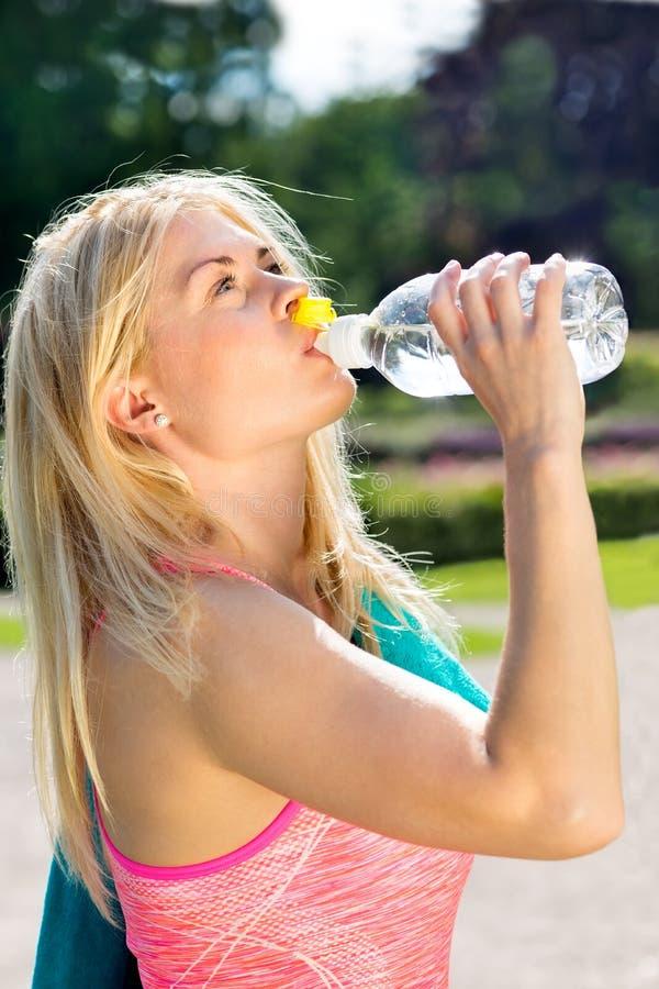 Törstig passformkvinna som sväljer ner vatten från flaskan arkivbilder