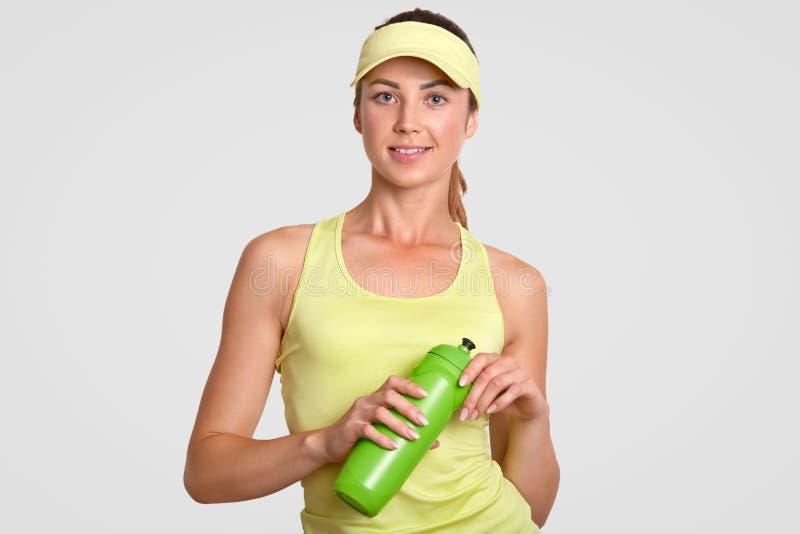 Törstiga härliga aktiva kvinnatagande bryter, når de har spelat tennis, den iklädda tillfälliga sportswearen, hållflaska med vatt royaltyfri bild