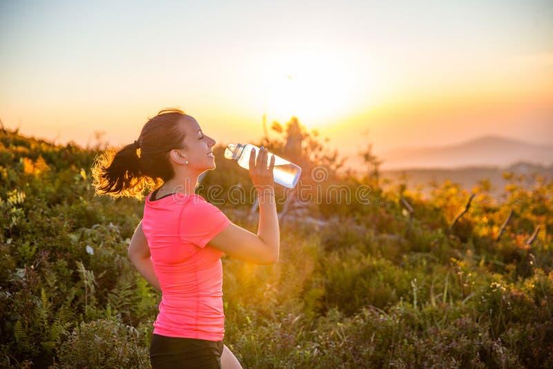 Törstigt dricksvatten för kvinnaslingalöpare från vattenflaskan royaltyfria bilder