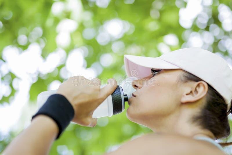Törstigt dricksvatten för ung kvinna, medan vila arkivbilder