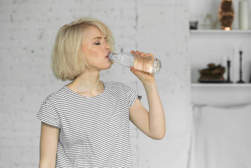 Törstigt gulligt flickadrinkvatten från flaskan arkivfoto